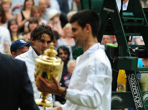 03 07 2011  Wimbledon, England. 2011 AELTC London ITF Grand Slam Tennis Tournament Mens Final  Award Ceremony. Novak Djokovic  of Serbia receives his winners cup and Rafael Nadal of Spain wtaches in the background