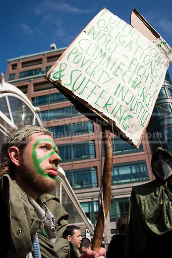 A Climate Rush activist waits for other demonstrators outside Liverpool Street Station. Protesters converged on the Bank of England from four start points across central London.