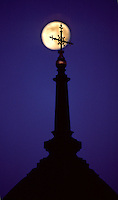 Eerie image of a full moon as it passes behind an ornate cross atop a church steeple.