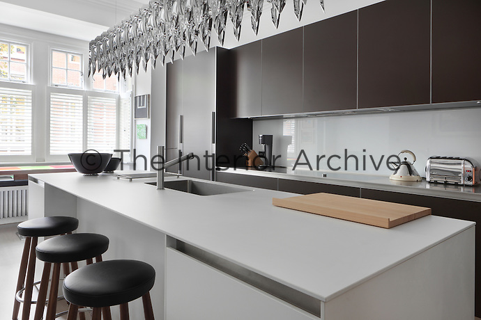The minimal matt surfaces of the these units compliment the complex shining shapes of a Hani Rashid light fitting in this Bulthaup and Zumtobel kitchen