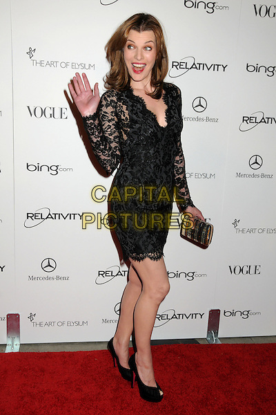 "MILLA JOVOVICH.attends the Art of Elysium 4th Annual Charity Gala ""Heaven"" held at The Annenberg Building at The California Science Center in Los Angeles, California, USA, January 15th 2011..full length black lace sleeve dress peep toe shoes clutch bag silver gold sequined sequin platform hand waving mouth open funny .CAP/ADM/BP.©Byron Purvis/AdMedia/Capital Pictures."