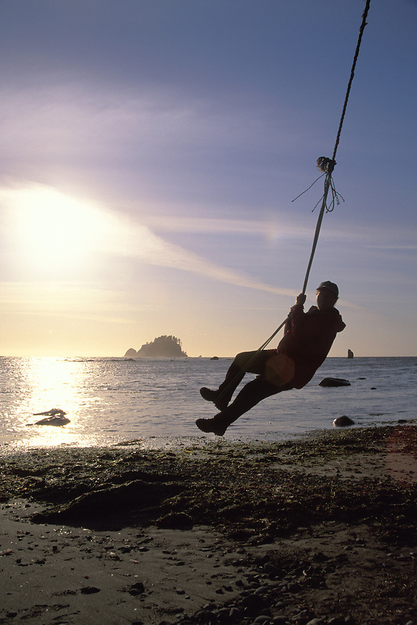 Woman swinging on rope swing, Cape Alava, Pacific Ocean, Olympic National Park, Washington