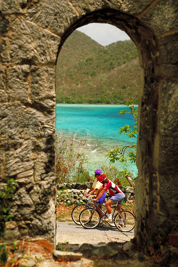 bike riders viewed through arched stone window of Annaberg ruins St. John. St John, US Virgin Islands Caribbean.