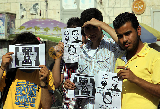 Palestinian protestors hold pictures of Palestinian prisoners Mahmoud al-Sarsak and Akram al-Rikhawi, whose are still refusing food for 80 days after a deal was made to end a mass prisoner hunger strike, during a demonstration in their support in the West Bank city of Nablus on 03 June, 2012. Photo by Nedal Eshtayah
