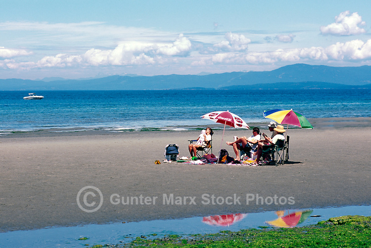 "A Family sunbathing on the Beach at Qualicum Beach, in the ""Oceanside Region"" of Vancouver Island, British Columbia, Canada"