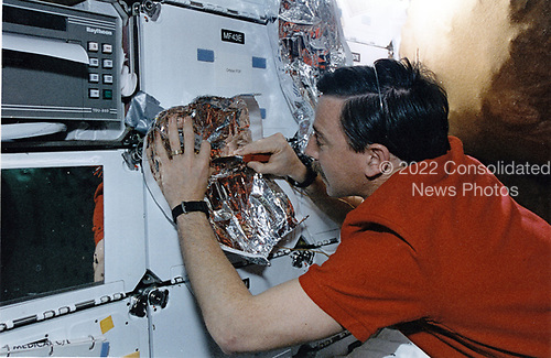On Discovery's mid deck, astronaut Scott J. Horowitz, STS-82 pilot, works on one of the MLI patches to be used by two crew mates on an upcoming space walk to repair worn insulation on the Hubble Space Telescope (HST).<br /> Credit: NASA via CNP