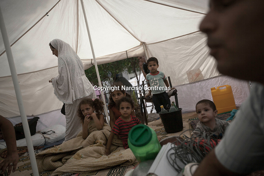 """In this Friday, Aug. 15, 2014 photo, the family of Ashaf Abu Kuamar (not pictured) sit inside a tent in a temporary shelter set up around Al-Shifa hospital as their home remains in ruins after it was completely destroyed during the """"Protective Edge"""" Israeli military operation in Shuyaja neighborhood in Gaza City. After a five days truce was declared on 13th August between Hamas and Israel, civilian population went back to what remains from their houses and goods in Gaza Strip. (Photo/Narciso Contreras)"""