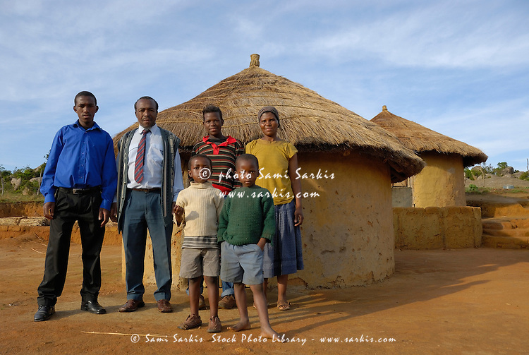 Family standing outside traditional huts in Ezulwini Valley, Swaziland, Africa.