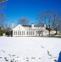 The facade of the house seen from across the lawn which is covered in snow