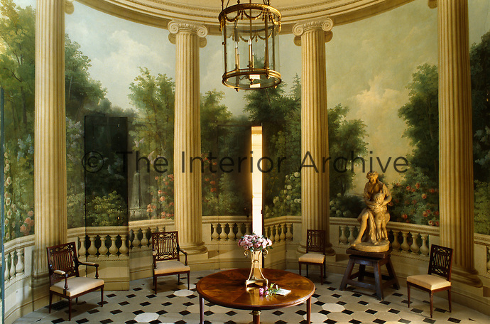 Flowers and woodland groves between the trompe l'oeil columns and balustrade cover the walls of the rotunda which is furnished with Etruscan-style mahogany seats