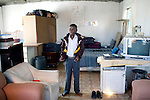 CAPE TOWN, SOUTH AFRICA - MARCH 15: Sikhumbuzo Hlahleni, age 15, a student at Cape Town City Ballet's youth company dress in his school uniform in his family house on March 15, 2010 in Khayelitsha, South Africa. He trains in Cape Town every Saturday. He also trains a few days week at home in Khayelitsha, a poor township outside Cape Town. He has to change taxi three times to get to the school. (Photo by Per-Anders Pettersson).