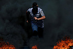 A masked Palestinian protester jumps up burning tires during clashes with Israeli troops following a demonstration near the Jewish settlement of Beit El, near Ramallah, in the occupied West Bank June 29, 2018. Photo by Shadi Hatem