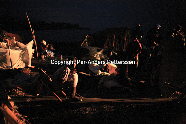 MALUKU, DEMOCRATIC REPUBLIC OF CONGO JULY 3: Guelor Itambe, age 18, tries to sleep in a chair while traveling on a boat made of big trees on the Congo River on July 3, 2006 outside Mbandaka, Congo, DRC. The boat traveled with about 150 passengers from Bumba to Kinshasa, a journey of about 1300 kilometers. The Congo River is a lifeline for millions of people, who depend on it for transport and trade. Passengers slept in the open, with their goats, pigs and other animals. Boat travel is the only option for most people along the river as there?s no roads or infrastructure. Very few can afford to fly in a plane to the capital Kinshasa. During the Mobuto era, big boats run by the state company ONATRA dominated the river. These boats had cabins and restaurants etc. All the boats are now private and are mainly barges that transport goods. The crews sell tickets to passengers who travel in very bad conditions. The conditions on the boats often resemble conditions in a refugee camp. Congo is planning to hold general elections by July 2006, the first democratic elections in forty years. The Congolese and the international community are hoping that Congo will finally have piece and the country will be rebuilt..(Photo by Per-Anders Pettersson/Getty Images).