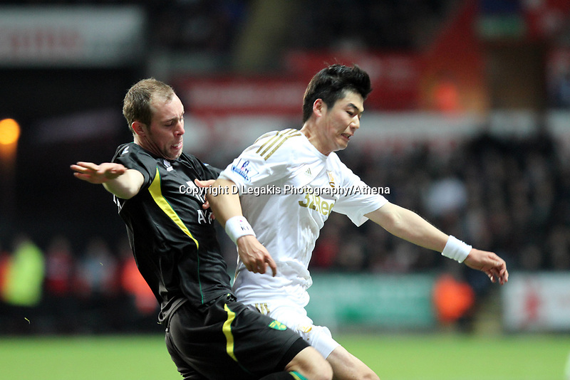 Barclays Premier League, Swansea City (White) V Norwich City (black) Liberty Stadium, Swansea, 08/12/12<br /> Pictured: Swansea's Ki Sung Yeung tackled by Grant Holt.<br /> Picture by: Ben Wyeth / Athena <br /> Athena Picture Agency<br /> info@athena-pictures.com