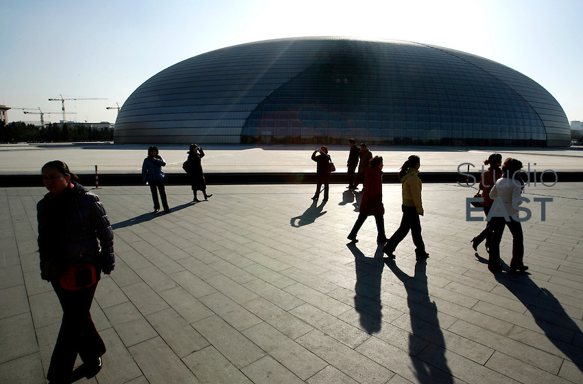 Pedestrians walk past Beijing National Grand Theatre in Beijing, China, on November 20, 2008. The National Centre for the Performing Arts was designed by French architect Paul Andreu. Completed in 2007, the 219.400 square meter building houses an opera house (2416 seats), a concert hall (2017 seats) and two theatres (one of 1040 seats) included in a titanium and glass shell which houses the public space. The concept of the National Centre for the Performing Arts is a cultural island in the middle of a lake. Photo by Lucas Schifres/Pictobank