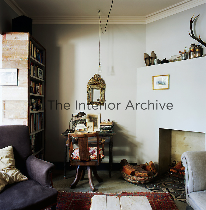 A snug sitting room where antique pieces sit happily with reclaimed and recycled materials. A fireplace has been reintroduced using Portuguese tiles as a base. A bookcase made from reclaimed wood stands in one corner.