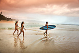 USA, Oahu, Hawaii, Kyla Tipps, Logan Garcia and Tyson Tynanes walk out to the surf at Pipeline Beach on the North Shore