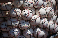 A collection of baseballs sit in a netted hopper, in sunlight, on a baseball diamond, before batting practice.