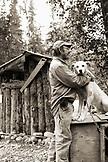 USA, Alaska, Talkeetna, Iditarod musher Randy Cummins hugs one of his sled dogs Traveler, Huskytown