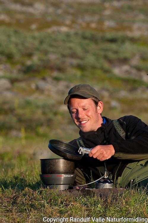 Mann koker vann på primus. ---- Man boiling water.