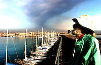 Il porto di Catania e la cappa sulla città della cenere vulcanica durante l'eruzione dell'Etna nel 2002.