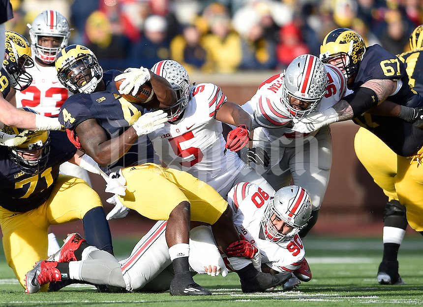 Michigan Wolverines running back De'Veon Smith (4) gets wrapped up by Ohio State Buckeyes defensive lineman Tommy Schutt (90) and Ohio State Buckeyes linebacker Raekwon McMillan (5) in the fourth quarter of the college football game between the Michigan Wolverines and the Ohio State Buckeyes at Michigan Stadium in Ann Arbor, Saturday afternoon, November 28, 2015. The Ohio State Buckeyes defeated the Michigan Wolverines 42 - 13. (The Columbus Dispatch / Eamon Queeney)