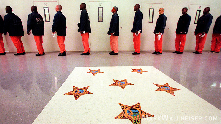 A Leon County Boot Camp platoon lines up along a wall by .the doors to their rooms with toothbrushes and wash cloths in .hand to go to the wash room to brush their teeth after lunch. The .white square in the center of the barricks with the Sherrif's .stars represents society and it's rules and the boot camp .offenders are NEVER allowed to step on it..