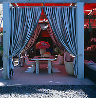 The outdoor dining area is enclosed with dramatic striped curtains and sits on a concrete 'rug' surrounded by dark grey Mexican pebbles
