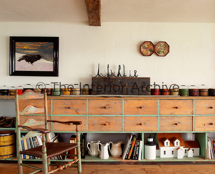 A rustic sideboard of drawers and open shelves displaying a row of small wooden buckets lines one wall of the kitchen