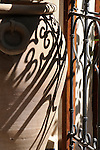 Shadows from an iron fence on a pot in a patio Marrakesh, Morocco.
