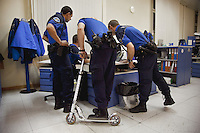 Switzerland. Geneva. Paquis police station. Four police officers check on a computer the identity of a man who was arrested. A policeman is using a scooter to move from one side to the other of the police station. Three policemen have a two-way radio which is a radio that can both transmit and receive (a transceiver). A two-way radio (transceiver) allows the operator to have a conversation with other similar radios operating on the same radio frequency (channel). Two-way radios are available with hand-held portable configurations. Hand-held radios are often called walkie-talkies or handie-talkies. A police station or station house is a building which serves police officers and contains offices, temporary holding cells and interview/interrogation rooms. 16.03.12 © 2012 Didier Ruef