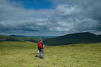 A walker looking across Culter reservoir to Culter Fell, Tinto Hill and the Clyde Valley from Gathersnow Hill, South Lanarkshire, Scotland<br /> <br /> Copyright www.scottishhorizons.co.uk/Keith Fergus 2011 All Rights Reserved