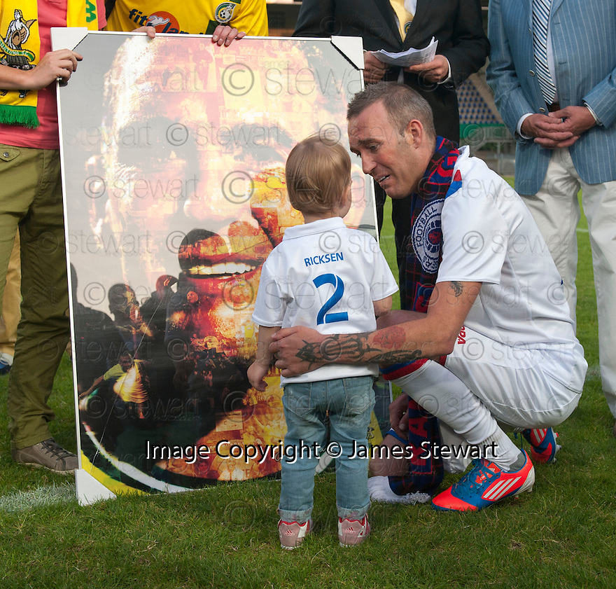 Fernando Ricksen Testimonial :  Fernando Ricksen shows his daughter, Isabella, a mosaic presented to him by Fortuna Sittard players.