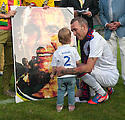Fernando Ricksen Testimonial :  Fernando Ricksen shows his daughter, Isabella, a mosaic presented to him by Fortuna Sittard players.