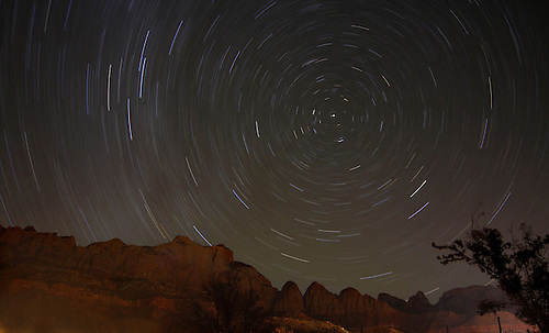 Stars revolve around the North Star in a circular motion during the nighttime sky at Zion National Park, Utah