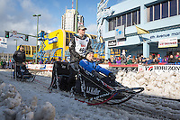 Dallas Seavey and team leave the ceremonial start line with an Iditarider at 4th Avenue and D street in downtown Anchorage, Alaska during the 2015 Iditarod race. Photo by Jim Kohl/IditarodPhotos.com
