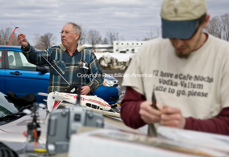 TORRINGTON, CT - 02 MARCH 2010 -030210JT05--<br /> Tim Seebach, of Torrington, sets up his battery-powered park flyer airplane as Jeff Davis, right, fixes a remote control helicopter he had just crashed at the Bishop Donnelly Sports Complex in Torrington on Tuesday, taking advantage of the day's calm winds.<br /> Josalee Thrift Republican-American