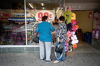 Shoppers browse the windows of a 99 cent store along Main Street in downtown McAllen, Texas, Saturday, April 3, 2010. Downtown McAllen stores don't sell designer or name brand items, but still reach a wide customer base for McAllen residents and visiting Mexican tourists. ..PHOTO/ Matt Nager