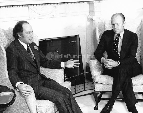 United States President Gerald R. Ford, right, meets Prime Minister Pierre Elliott Trudeau of Canada, left, in the Oval Office of the White House in Washington, DC on December 4, 1974.   The meeting was centered around oil and livestock.  Canada recently decided to phase out exports of oil to the US.  The US and Canada will still meet to resolve the dispute over Canada's ban on certain beef imports from the US.  The ban prompted the President to retaliate against Canadian meat imports.<br /> Credit: Barry A. Soorenko / CNP /MediaPunch