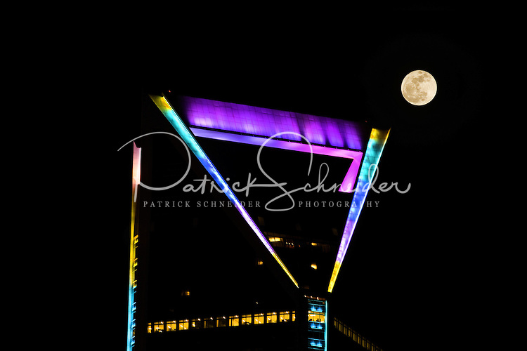 The full moon hangs over Charlotte's Duke Energy Tower in downtown Charlotte, NC. Actual photo, moon was not placed on image using PhotoShop or other photo editing software. The Duke Energy Center stands 786 feet tall with 48 floors (54 floors including the mechanical floors). Completed in 2010, it is the second-largest building in Charlotte. The Duke tower is illuminated by hundreds of programmable color LED (light-emitting diodes) and metal halide luminaries, which allow the colors of the building to be changed for visual interest and artistic effect.