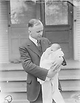 MATCHING HAIRLINES. This father looks appropriately enthralled, while his baby yawns.<br />