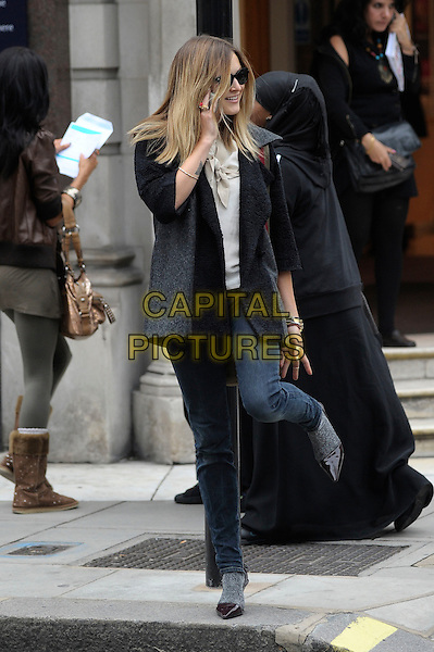 FEARNE COTTON.Seen leaving work at BBC Radio 1 Studios, London, England, UK, .October 5th 2010..full length grey gray coat jeans blue green khaki shoulder canvas bag socks grey gray shoes pointy pointed standing on one foot leg talking on mobile phone .CAP/DYL.©Dylan/Capital Pictures.