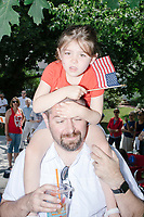 A girl holds an American flag while sitting on a man's shoulders as they watch the 4th of July Parade in Amherst, New Hampshire, on Thu., July 4, 2019.