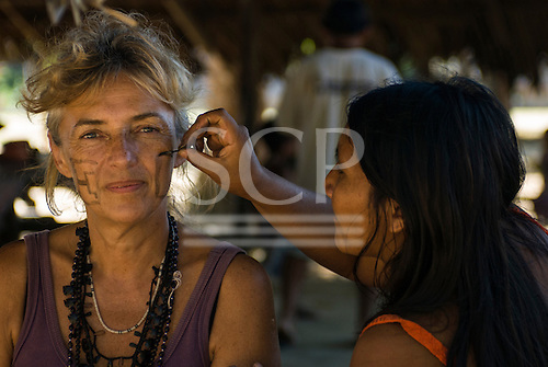 Xingu Indigenous Park, Mato Grosso State, Brazil. Aldeia Capivara (Kaiabi). Kuianre-Ayup Kaiabi painting Sue Cunningham's face with genipapu dye.