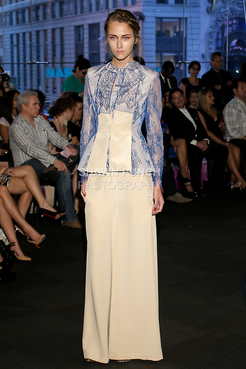 "Model walks runway in a beige and dark blue lace blazer with beige palazzo pants, from the Yuna Yang Spring Summer 2013 ""Close your eyes and see the world"" collection, at the NASDAQ Marketsite, during New York Fashion Week, on September 7, 2012."