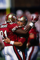 SAN FRANCISCO, CA - Quarterback Steve Young of the San Francisco 49ers hugs Terrell Owens during a game against the St. Louis Rams at Candlestick Park in San Francisco, California in 1997. Photo by Brad Mangin