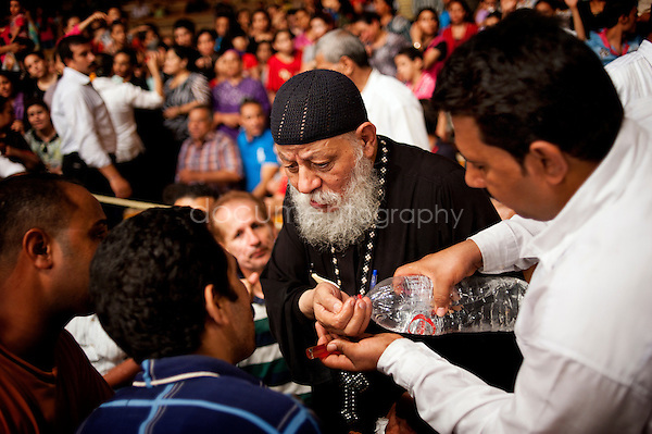 Followed by one of his devoted carrying bottles filled with holy water, Father Samaan uses it to throw in the faces of men and women coming to receive from him exorcism session.<br /> <br />  copyright : Magali Corouge / Documentography