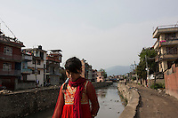 Nepal - Kathmandu - A little girl walks by a popular neighborhood of the capital. According to UN figures, 7,2 million Nepalis work abroad (4 millions of them in India). Half of them are undocumented, 1700 migrant workers leave Nepal every day, 2/3 dead bodies arrive at Kathmandu airport every day. According to the World Bank, in 2013 Nepal received more than 5 billion USD in remittances from abroad. This constitutes 24.7 percent of the GDP, the third highest percentage in the world after Tajikistan and Kyrgyzstan. A third of all Nepali households, and 35% of rural households, have at least one member working and living abroad. 24.8 percent of Nepalis still live under the poverty line. Nepali GDP per capita (PPP) stands at 1,102 USD, the twentieth lowest in the world. Since 1971, Nepal has been classified as one of the 48 least developed countries by the UN.