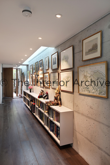 A modern entrance hallway with exposed concrete walls and wooden floor. A collection of maps and paintings hang on the wall above book shelves.