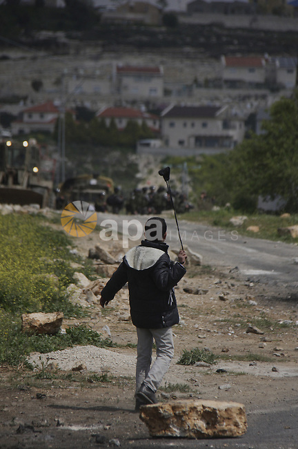 A Palestinian protester throws stones at Israeli soldiers during a demonstration to mark the anniversary of Land Day in the village Kafr Qaddum, close to the northern town of Nablus in the occupied Israeli West bank on March 30, 2012. Land Day mark the annual event that commemorates the deaths of six Arab Israeli protesters at the hands of Israeli forces during mass demonstrations in 1976 against plans to confiscate Arab land in northern Israel. Photo by Wagdi Eshtayah